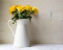 在一个白色水罐的黄色玫瑰 图库摄影