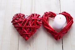 在一个的两红色心脏是在木背景点燃的一个蜡烛,华伦泰` s天,假日爱 免版税库存照片