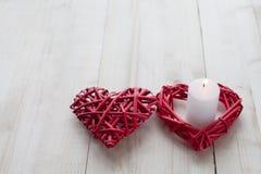 在一个的两红色心脏是在木背景点燃的一个蜡烛,华伦泰` s天,假日爱 免版税库存图片