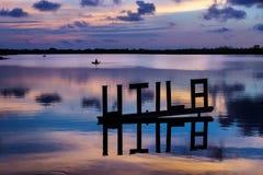 在一个盐水湖的日落有Utila与kanu的信件标志的在背景, Utila,洪都拉斯,中美洲中 免版税图库摄影