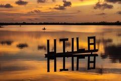 在一个盐水湖的日落有Utila与kanu的信件标志的在背景, Utila,洪都拉斯,中美洲中 免版税库存照片