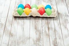 在一个盘子的五颜六色的复活节彩蛋在木背景 文本的空间 看板卡复活节 库存图片