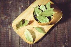 在一个盘子的月桂叶在一片木碗/月桂叶在农村样式在a 库存图片