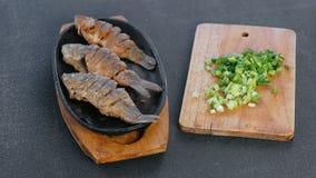在一个盘子的油煎的鱼鲤鱼在一根黑桌和葱上在委员会 大盘子 股票视频