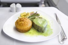 在一个盘子的集合航空餐牛排,在一张白色桌上 免版税库存照片