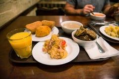 在一个盘子的Rdinary食物在桌上在自助食堂 免版税库存图片