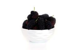 在一个盘的桑树与隔绝在白色背景黑莓 图库摄影