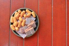 在一个盘的火腿香肠在一个红色木地板上 免版税库存照片