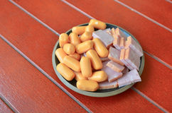 在一个盘的火腿香肠在一个红色木地板上 免版税库存图片