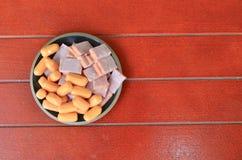 在一个盘的火腿香肠在一个红色木地板上 库存照片
