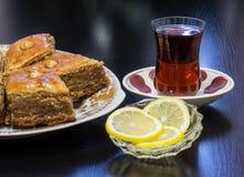 在一个盛肉盘的巴库果仁蜜酥饼用茶涌入了一杯Armud和柠檬 免版税库存照片