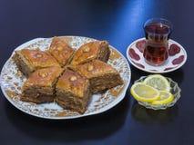 在一个盛肉盘的巴库果仁蜜酥饼用茶涌入了一杯Armud和柠檬 库存照片