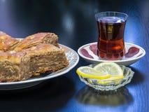 在一个盛肉盘的巴库果仁蜜酥饼用茶涌入了一杯Armud和柠檬 免版税库存图片
