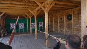 在一个目标的一个人射击从在破折号的一张石弓 慢动作锁着的手扶的射击 箭头目标射击 股票视频
