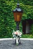 在一个石圈子的婚礼花束在葡萄酒街灯下 免版税图库摄影