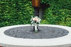 在一个石圈子的婚礼花束在葡萄酒街灯下 库存照片