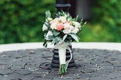 在一个石圈子的婚礼花束在葡萄酒街灯下 图库摄影