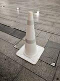 在一个石块地板上的白色塑料交通锥体 免版税库存照片