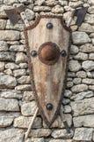 在一个石墙上的古老武器 有铁口音的木盾 免版税库存图片