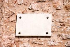 在一个石墙上的白色大理石标志 免版税库存照片