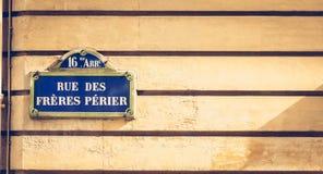 在一个石墙上的蓝色巴黎人路牌 库存照片