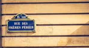 在一个石墙上的蓝色巴黎人路牌 免版税库存图片