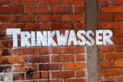 在一个石墙上绘的饮用水上写字 免版税库存照片