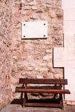 在一个石墙和长木凳上的白色大理石标志 库存照片