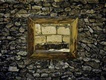 在一个石墙的古老窗口用在绝望砖墙上的酒  库存照片