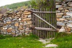 在一个石墙的土气手工制造木门 免版税图库摄影