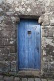在一个石墙的老蓝色木门 免版税库存照片
