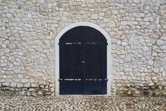 在一个石墙的老门 免版税库存照片