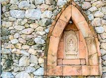在一个石墙的菩萨雕象 图库摄影