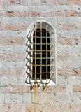 在一个石墙的被成拱形的老窗口 免版税库存照片