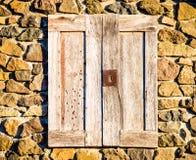 在一个石墙的被风化的木快门 免版税库存照片