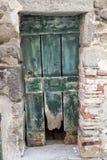 在一个石墙的褴褛老木门 意大利加尔达湖 对一个房子的入口在村庄 库存照片