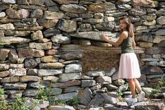 在一个石墙附近的少妇 免版税库存图片