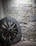 在一个石墙附近的木轮子 免版税库存照片