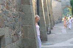 在一个石墙附近的美丽的女孩 库存照片