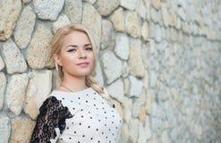 在一个石墙附近的美丽的女孩 免版税库存照片
