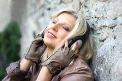在一个石墙附近的资深英俊的妇女有耳机的 免版税图库摄影