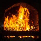 在一个石壁炉的开头的明亮和热的火焰 库存图片