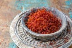 在一个石碗的干有机红色番红花香料在木backgr 免版税图库摄影
