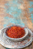 在一个石碗的干有机红色番红花香料在木backgr 免版税库存图片