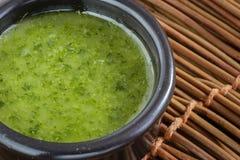 在一个石碗的自创绿色调味汁用荷兰芹、大蒜、橄榄油和盐 免版税库存照片