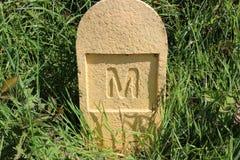 在一个石路标志的信件M,爱尔兰 免版税库存图片