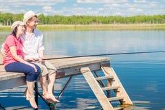 在一个码头的一对已婚夫妇有抓鱼的赤脚的 库存照片