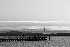 在一个码头的妇女剪影在日落的一个湖 免版税图库摄影