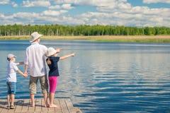 在一个码头的愉快的家庭在美丽如画附近 免版税库存图片