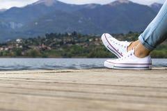 在一个码头的女孩腿有蓝色牛仔裤和白色鞋子的 免版税库存照片